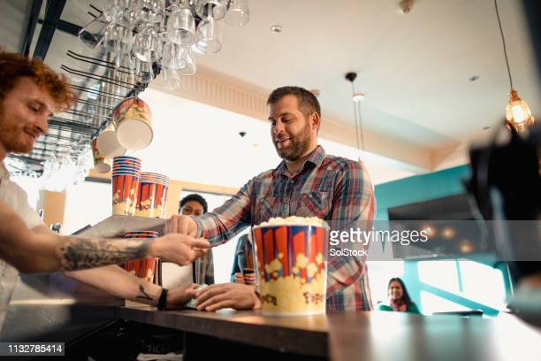 paying for popcorn - film industry stock pictures, royalty-free photos & images