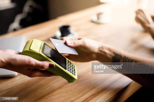 paying the bill with contactless credit card - credit card stock pictures, royalty-free photos & images