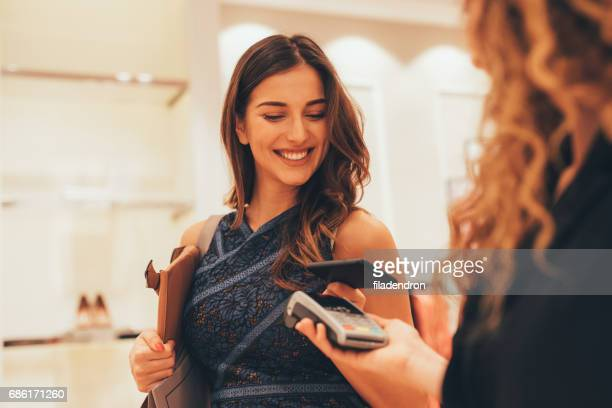 paying via smart phone at a clothing store - satisfaction stock pictures, royalty-free photos & images