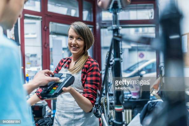 paying with a credit card - bicycle shop stock pictures, royalty-free photos & images