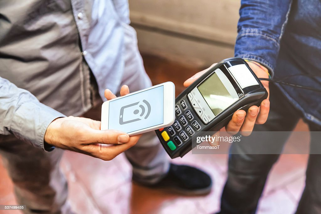 Paying with a smart phone using NFC technology : Stock Photo