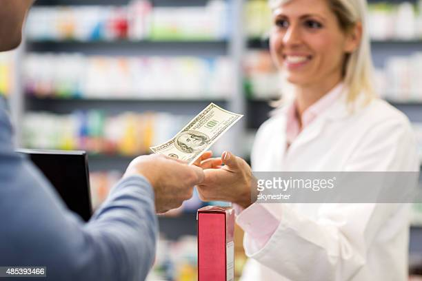 Paying with cash in a pharmacy.
