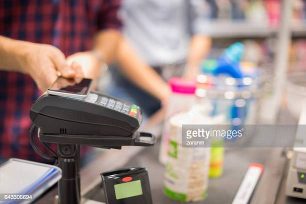 paying with smart phone - convenient store stock photos and pictures