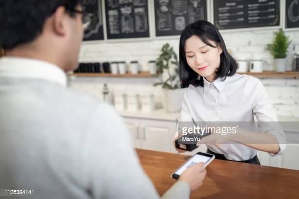 betalen met de smartphone in een cafe - china oost azië stockfoto's en -beelden
