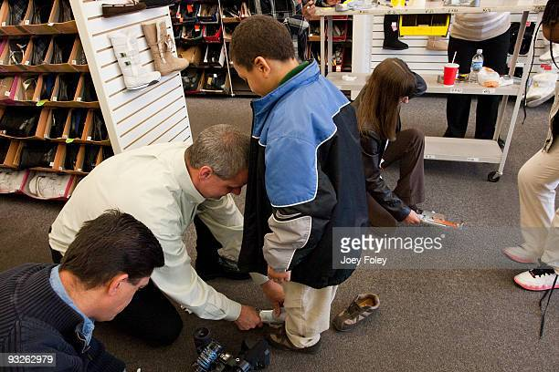 Payless employees measure children's feet with Brannock device at Payless ShoeSource on November 20 2009 in Cincinnati Ohio