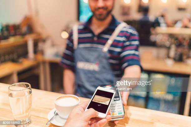 payment with mobile phone in cafeteria - nfc stock pictures, royalty-free photos & images