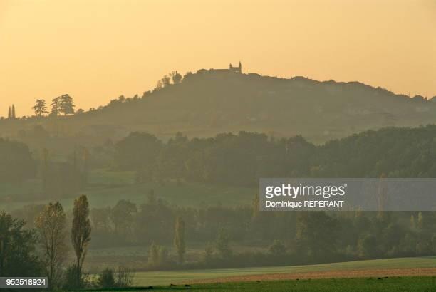 Paysage du Haut Agenais le village de Monflanquin vue lointaine a contrejour de la colline de Monflanquin au lever du soleil brume matinale et...