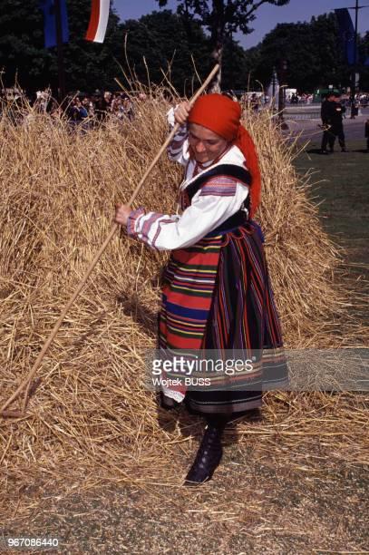 Paysanne en costume traditionnel pendant la Grande Moisson sur les ChampsElysées à Paris le 24 juin 1990 France