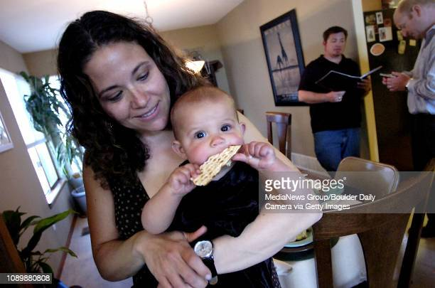 Payton Abbott eight months munches on matzoh while being held by her mother Stacey at a Passover dinner on Monday night in Superior In the background...