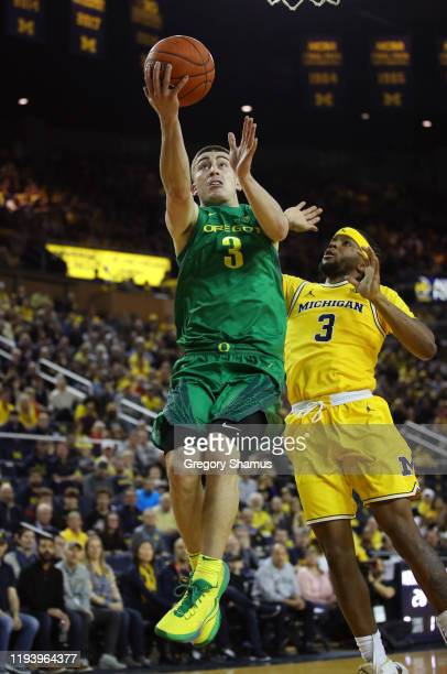 Payton Pritchard of the Oregon Ducks drives to the basket against Zavier Simpson of the Michigan Wolverines during the second half at Crisler Arena...