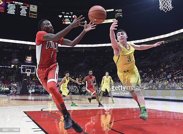 Payton Pritchard of the Oregon Ducks tips the ball away from Kris Clyburn of the UNLV Rebels during the first half of the game at the Moda Center on...