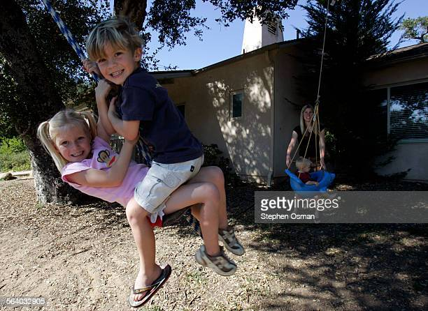 Payton Wolf 5 left and Kyle Tro 4 swing together while Ann Tro pushes her son Kaden 16 months on swing in background outside their home in the Las...
