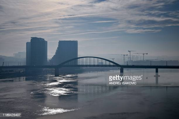 Pciture taken on December 18, 2019 shows buildings and cranes in background of a bridge over the Sava river, as heavy fog and air pollution dominate...