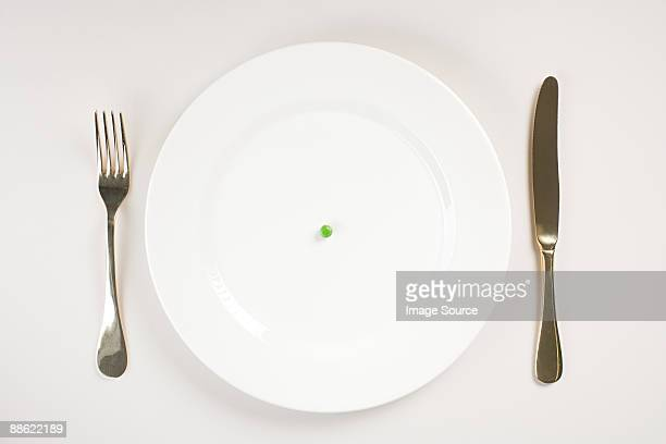 a pea on a plate - eating disorder stock pictures, royalty-free photos & images