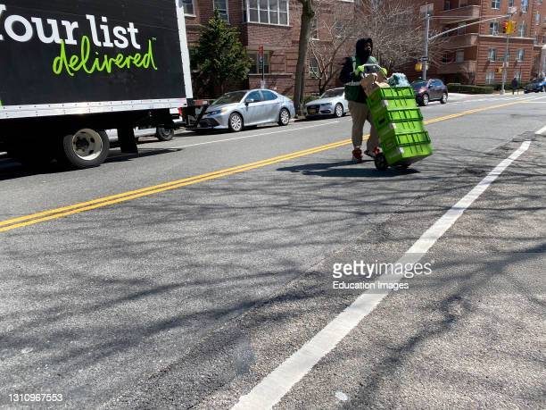 Pea Pod Delivery person with groceries on hand truck, Queens, New York.