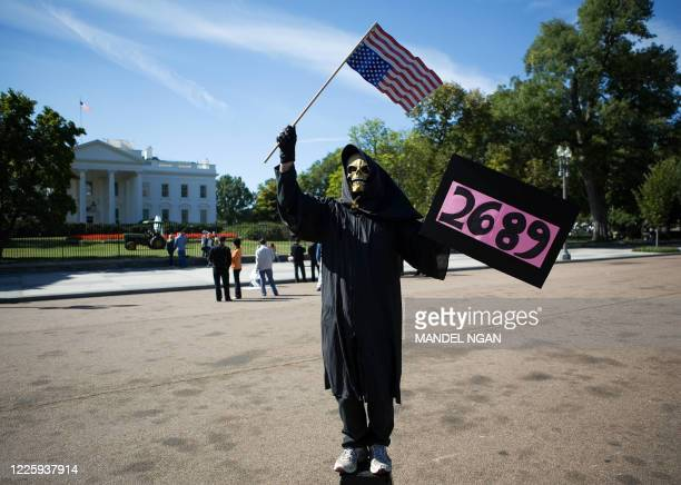 A peace activist dressed as the grim reaper stand on Pennsylvania Avenue infront of the White House 21 September 2006 in Washington DC US losses in...