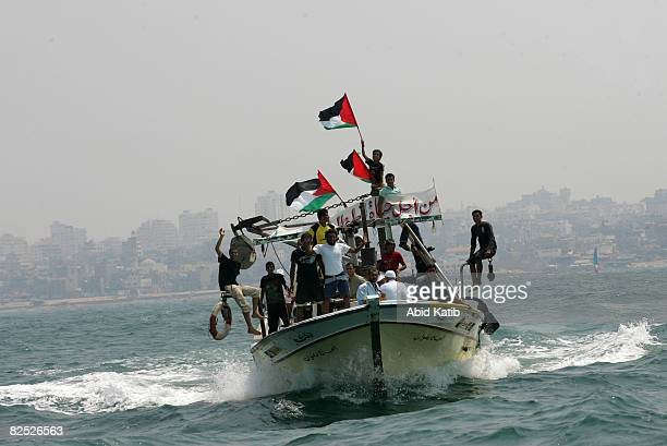 Peace activists locals and journalists ride on 16 fishing boats as they head out to sea to welcome two boats led by the USbased Free Gaza group...