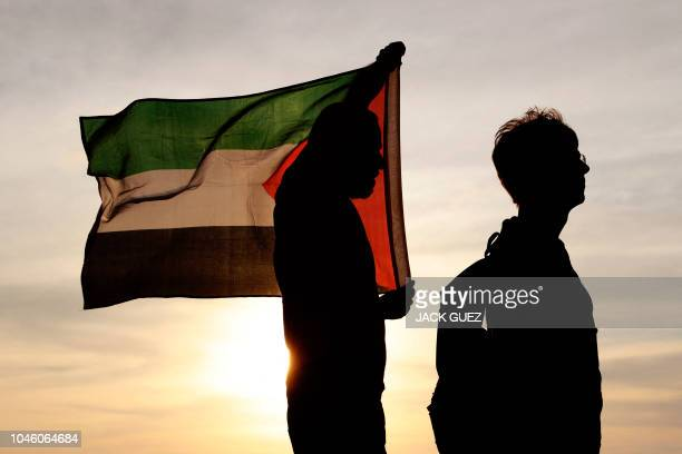 TOPSHOT Peace activists wave a Palestinian flag during a protest near the southern Israeli kibbutz of Nahal Oz near the border with the Gaza Strip on...
