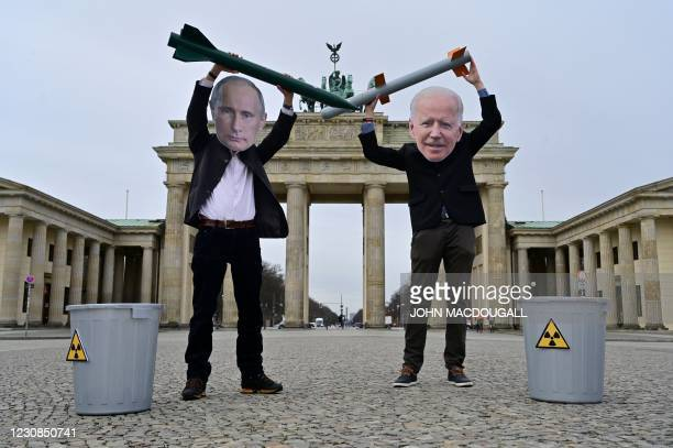 Peace activists wearing masks of Russian President Vladimir Putin and newly elected US President Joe Biden pose with mock nuclear missiles in front...
