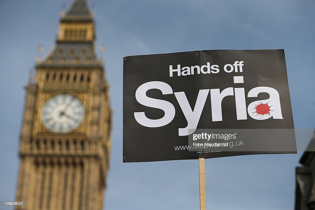 A peace campaigner hols up a placard outside Parliament on August 29, 2013 in London, England. Prime Minister David Cameron has recalled Parliament to debate the UK's response to a suspected chemical weapon attack in Syria.