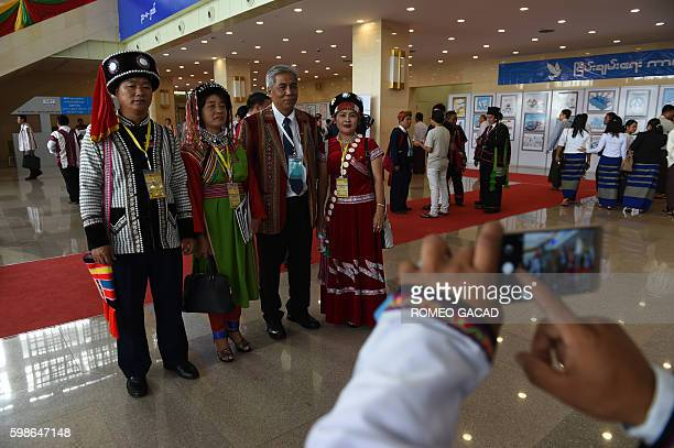 Peace conference delagate Ah Moe Si with other Lisu ethnic group members from upper Kachin State wearing a round black hat studded with circular...