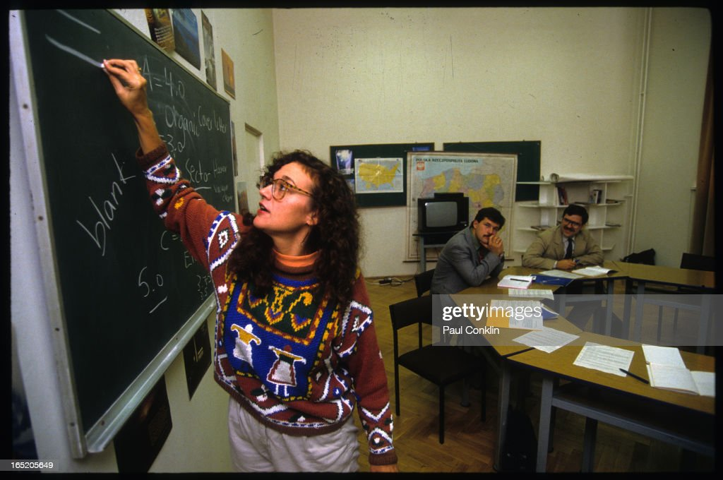 Peace Corps volunteer Mary Nolan writes on a blackboard as she teaches a class, Warsaw, Poland, 1980s.