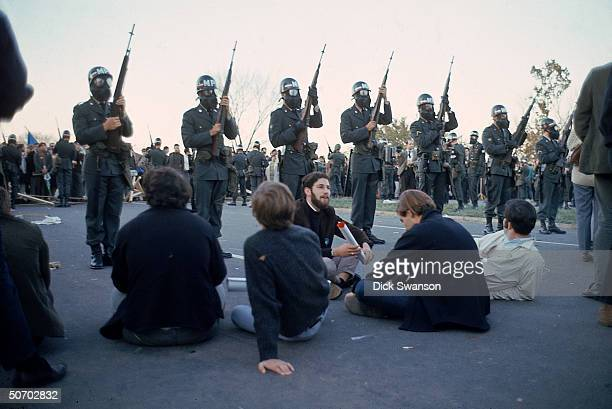 Peace demonstrators sitting in protest to the Vietnam War w military police in riot gear standing by