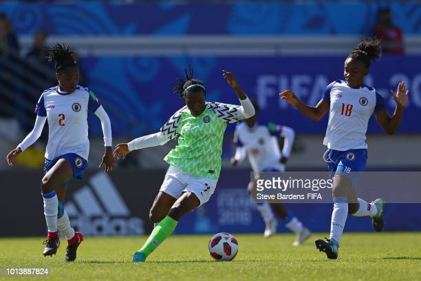 Peace Efih of Nigeria breaks away from Ruthnt Mathurin and Melchie Dumonay of Haiti during the FIFA U20 Women's World Cup France 2018 group D match...