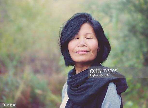 peace is bliss - smiling woman - asian 50 to 55 years old woman stock photos and pictures