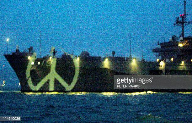 A peace symbol is illuminated on the bow of the USS Blue Ridge by Greenpeace protesters to remind the US of the overwhelming wish of Chinese people...