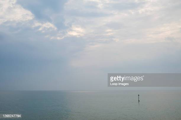 Peaceful cloudy sky over a calm sea containing a single groyne marker.