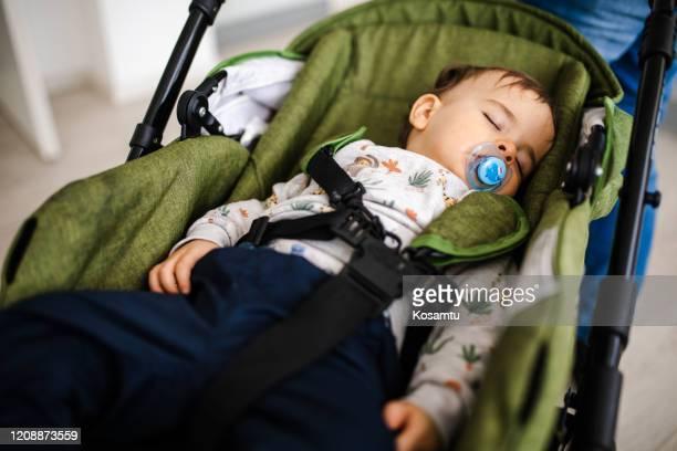 ベビーカーで眠って、甘い夢を見て平和なかわいい男の子 - 乳母車 ストックフォトと画像