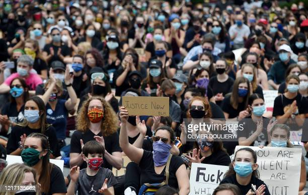 Peaceful demonstrators hold signs as they protest the death of George Floyd hold up placards outside the Bethesda Library on June 2, 2020 in...