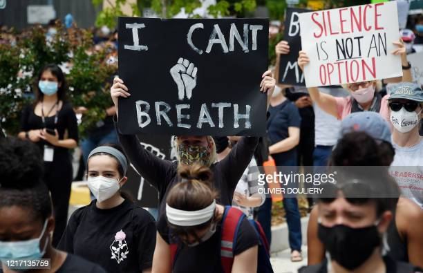 Peaceful demonstrators hold signs as they protest the death of George Floyd outside the Bethesda Library on June 2, 2020 in Bethesda, Maryland. -...