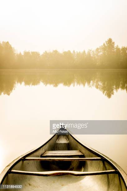 peaceful fishing lake and canoe at sunrise. - canoe stock pictures, royalty-free photos & images