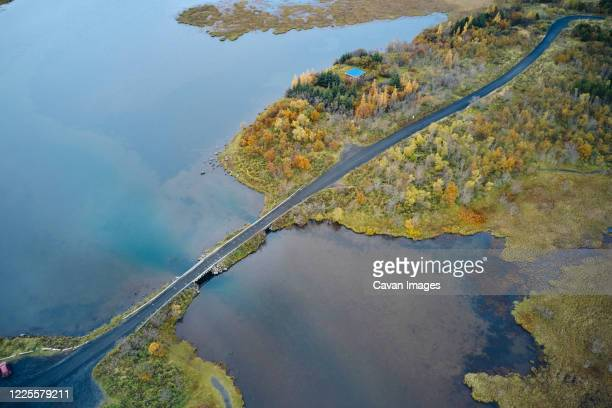 peaceful marsh with asphalt road - drainage_basin stock pictures, royalty-free photos & images