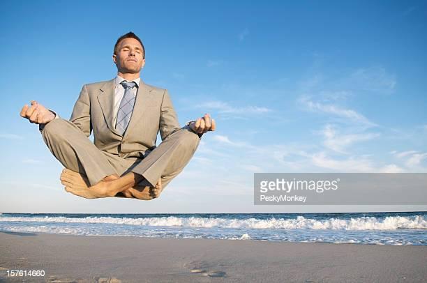 Paisible Homme d'affaires méditer Levitating au-dessus de la plage tranquille