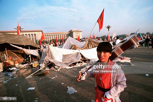 Peaceful musical protest. Early one morning a young woman carries a guitar through Tiananmen Square. Pro-democracy demonstrators and protestors...