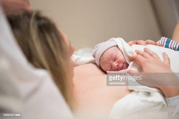 paisible nouveau-né à l'hôpital sur la poitrine de maman - accouchement photos et images de collection