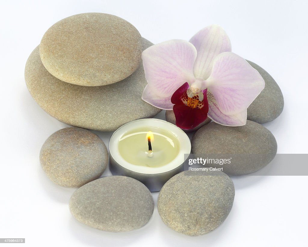 Peaceful orchid, pebble and candle composition : Stock Photo