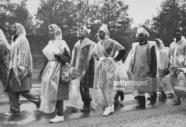Peaceful protesters, wearing plastic raincoats, marching to Montgomery in the pouring rain, Alabama, US, 25th March 1965.