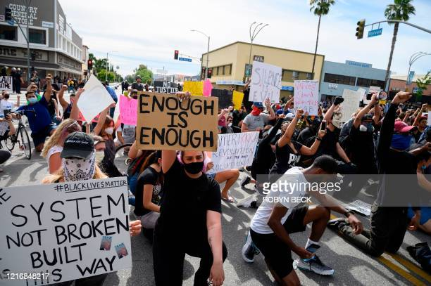 Peaceful protestors hold up placards as they demonstrate the killing of George Floyd on June 1 2020 in the Van Nuys neighborhood of Los Angeles after...