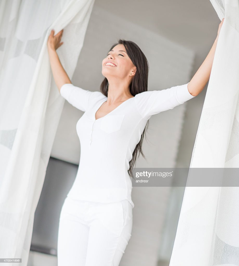Peaceful woman at home opening the window : Stock Photo