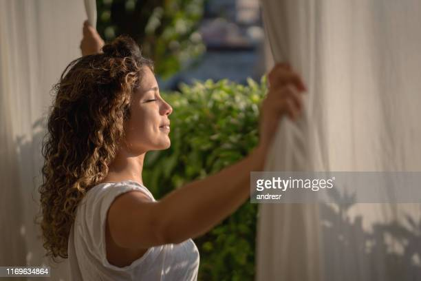 mulher calma que olha através de seu indicador do quarto na manhã - sunlight - fotografias e filmes do acervo