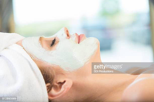 Peaceful woman relaxing during facial at tranquil spa