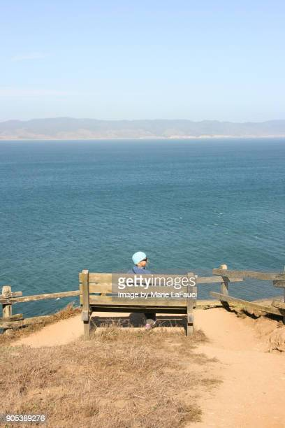 Peaceful woman sitting on bench looking at view of the Pacific Ocean