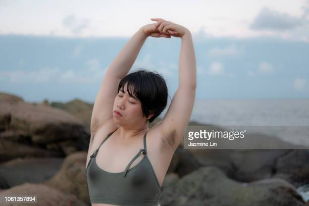 peaceful woman stretching with eyes closed and armpit hair - armpit hair stock-fotos und bilder
