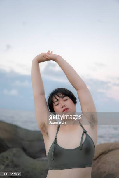 peaceful woman with armpit hair stretching with eyes closed - armpit hair stock-fotos und bilder