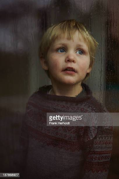 Peaceful young boy gazing out rainy window