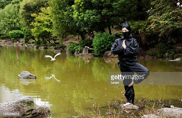 Peacefull Ninja meditating on a stone in a lake, Japan